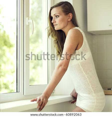 Portrait of beautiful pensive girl at window - stock photo