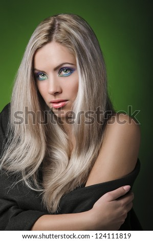 portrait of beautiful peroxide blonde girl on green background - stock photo