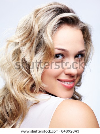 portrait of beautiful plus size curly young blond woman posing on gray - stock photo