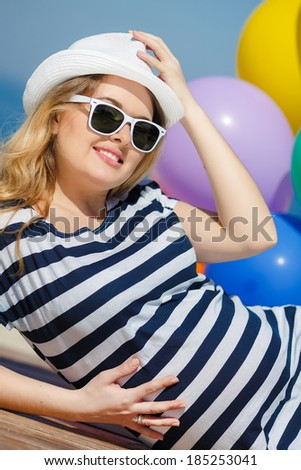 Portrait of beautiful pregnant woman in sunglasses and white hat with bright colorful balloons on sea shore background