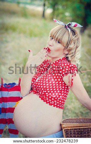 Portrait of beautiful pregnant woman in the park, pin-up style - stock photo
