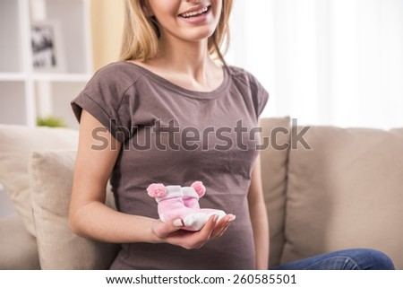Portrait of beautiful pregnant woman with her future baby's clothes. - stock photo