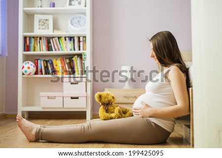 Portrait of beautiful pregnant woman with teddy bear sitting on the floor in bedroom - stock photo