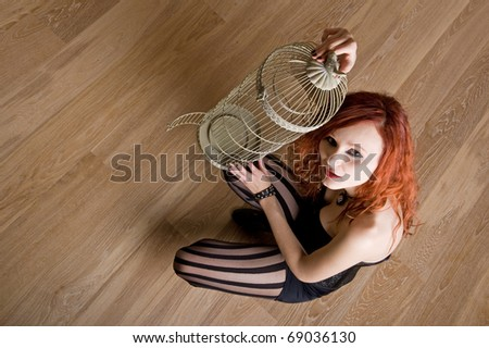 Portrait of beautiful red caucasian girl with bird cage. - stock photo