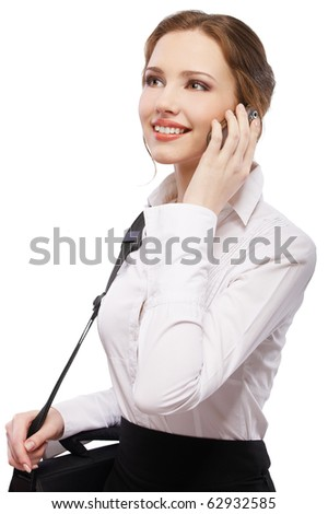 portrait of beautiful red-haired girl in white blouse with laptop bag making phone call - stock photo