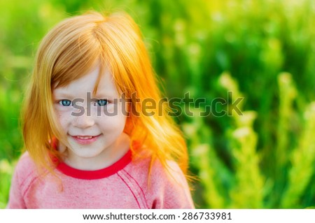 portrait of beautiful red-haired girl with big blue eyes and a sweet smile on background of green grass - stock photo