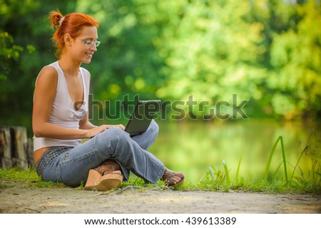 portrait of beautiful red-haired girl with laptop outdoors - stock photo