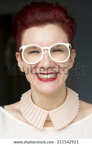 portrait of beautiful red-haired woman wearing white glasses and with a big smile