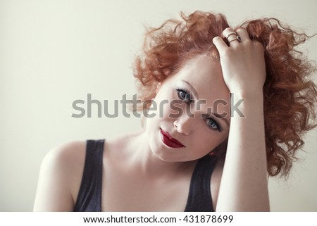 portrait of beautiful redhaired woman touching her curly hair - stock photo
