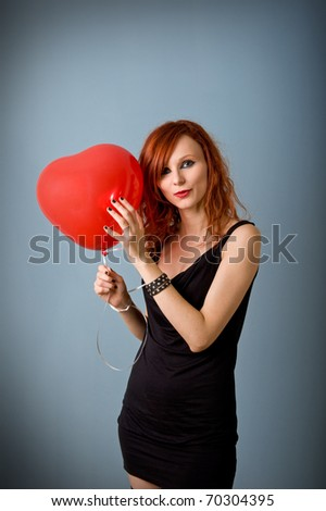 Portrait of beautiful redhead caucasian girl with heart balloon. - stock photo