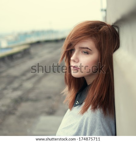 portrait of beautiful redhead girl on the roof - stock photo