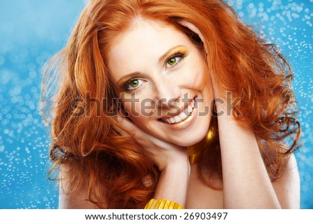 Portrait of beautiful redheaded girl on blue textured background - stock photo