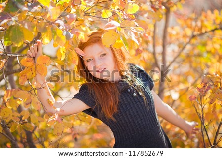 Portrait of beautiful redheaded girl walking outdoors in autumn