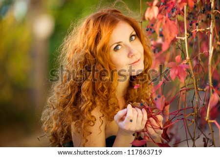 Portrait of beautiful redheaded woman walking outdoors in autumn - stock photo