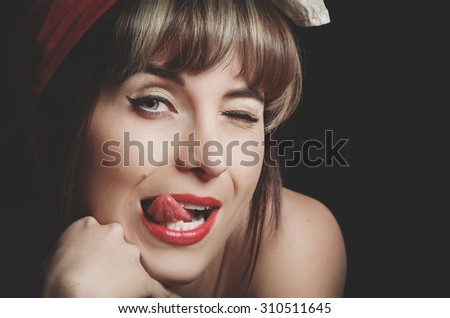 Portrait of beautiful retro girl licking her red lips