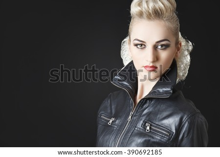 portrait of beautiful rocker girl wearing leather jacket and blonde hair - stock photo