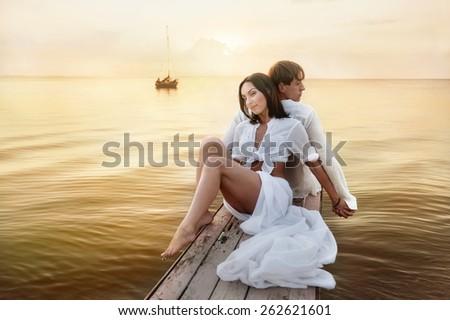 Portrait of beautiful romantic couple on background of sea sunset - stock photo