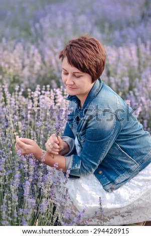 Portrait of beautiful romantic woman in fairy field of lavender with bouquet - stock photo
