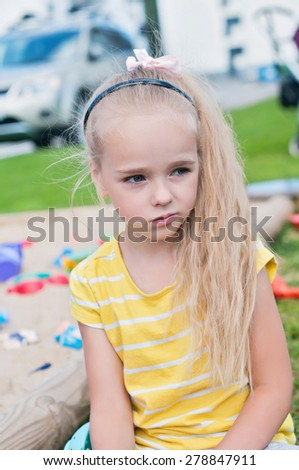 Portrait of beautiful sad little girl with long hair on the playground - stock photo