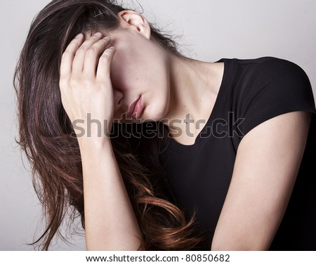 Portrait of beautiful sad woman with hair and hand on face - stock photo
