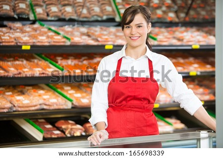 Portrait of beautiful saleswoman smiling while standing at counter in butcher's shop - stock photo