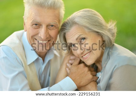 Portrait of beautiful senior couple embracing outdoors against green leaves background