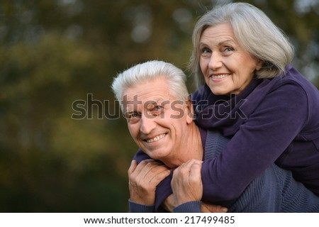 Portrait of beautiful senior couple embracing outdoors on the walk against green leaves background - stock photo