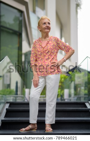 Portrait of beautiful senior tourist woman with blond hair relaxing around the city of Bangkok, Thailand