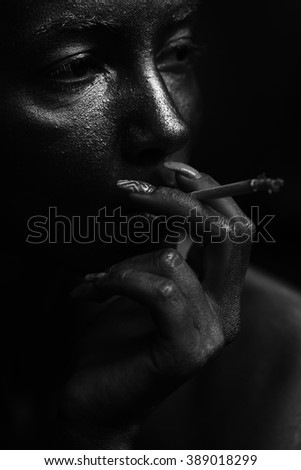 Portrait of beautiful sensual female face painted with silver of young sexual thoughtful woman smoking cigarette indoor in studio black and white, vertical picture