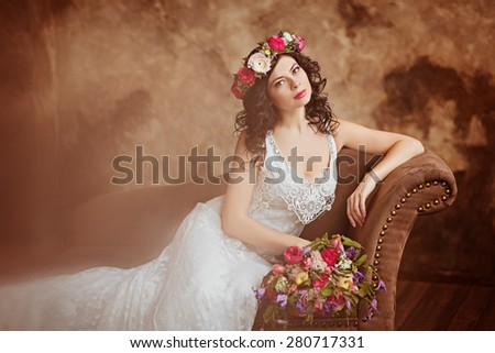 Portrait of beautiful sensual girls brunette in white lace dress, with a wreath of flowers on his head, sitting on the couch