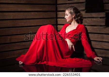 Portrait of Beautiful Sensual Woman in Long Fashion Red Dress sitting on floor over wooden background
