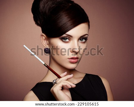 Portrait of beautiful sensual woman with elegant hairstyle.  Woman with cigarette Perfect makeup. Fashion photo - stock photo