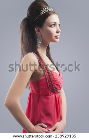Portrait of Beautiful Sensual Young Female with Crown Wearing Fashionable Pink Dress. Isolated Against Grey. Vertical Image