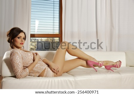 Portrait of beautiful sensuality and attractive sexy pretty female brunette woman posing in pink lingerie dress on the white couch on luxury style exclusive hotel apartment - stock photo