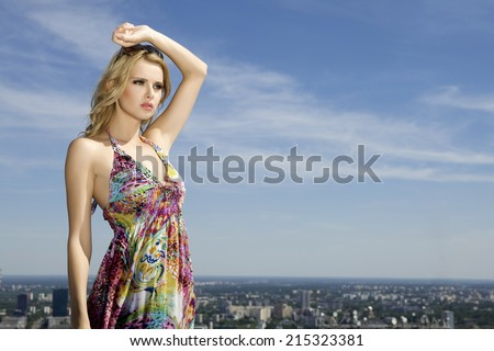 portrait of beautiful sensuality and attractive young adult blonde girl in sunglasses on background blue sky - stock photo
