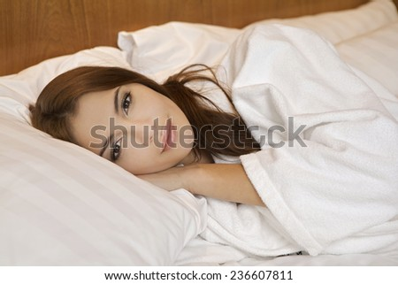 Portrait of beautiful sensuality and attractive young adult brunette woman sleeping in the white bed