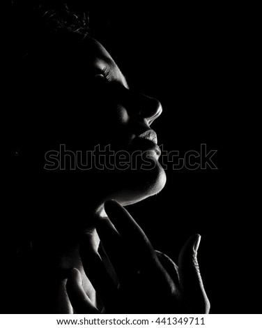 portrait of beautiful sensuality pensive girl profile with closed eyes in a dark, on a black background. body contour, black and white concept