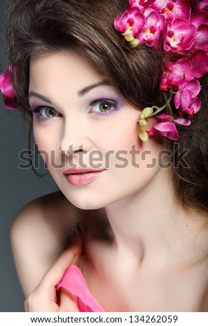 Portrait of beautiful sexual brunette with pink orchids in hairs. emotions, cosmetics - stock photo