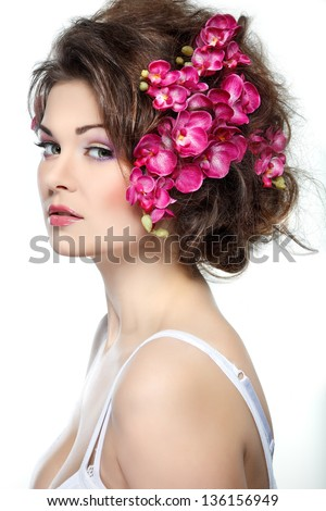 Portrait of beautiful sexual brunette with pink orchids in hairs. emotions, cosmetics