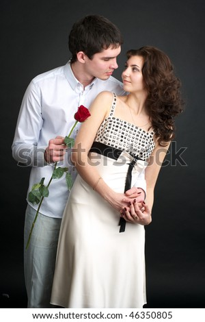 Portrait of beautiful sexual couple with red rose over black - stock photo