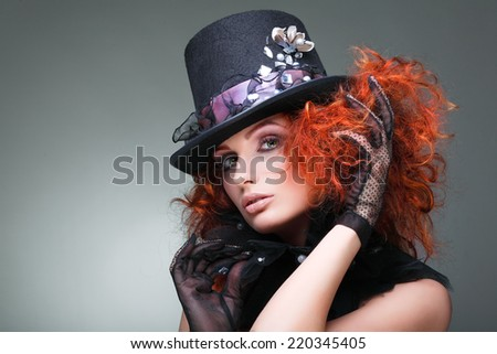 Portrait of beautiful sexual redheaded girl in a black hat on a grey background. Accessories. - stock photo