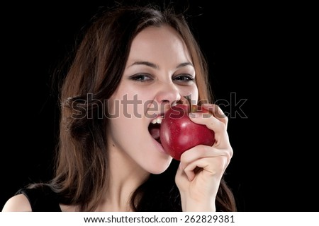 Portrait of beautiful sexy brunette girl on a black background with an apple