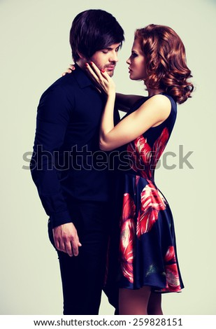 Portrait of beautiful sexy couple in love posing at studio in evening clothes. - stock photo