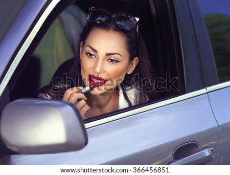 Portrait of beautiful sexy fashion girl model with red lips put lipstick looking in a mirror  driving car - stock photo