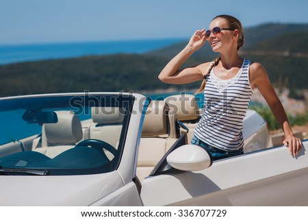 Portrait of beautiful sexy fashion woman model in sunglasses sitting in luxury white car with sea and sky background. Young woman driving on road trip on sunny summer day. Sea and sky. White cabrio. - stock photo
