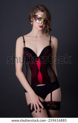 portrait of beautiful sexy woman in lingerie and mask over grey background - stock photo