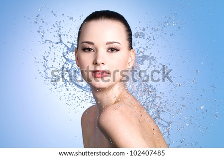 Portrait of beautiful sexy woman with splashes of water - colored background - stock photo
