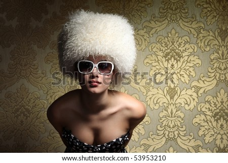 Portrait of beautiful sexy young woman in white fur hat posing over golden vintage floral wallpaper background. - stock photo