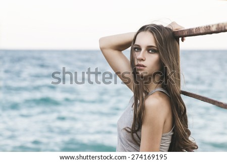 Portrait of beautiful sexy young woman posing at the beach with blue sky and white sand around, outdoor