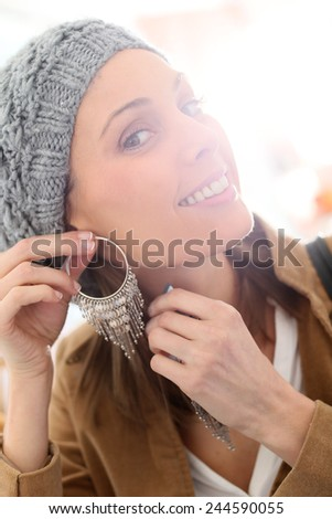 Portrait of beautiful shopping girl trying earings on
